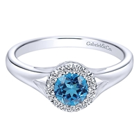 This stunning and simple blue topaz and diamond ring features diamond accents that surround a swiss blue topaz in this 14k white gold ring.