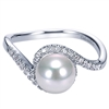 One pearl sits in the center of round diamond halo swirl in 14k white gold pearl and diamond ring.