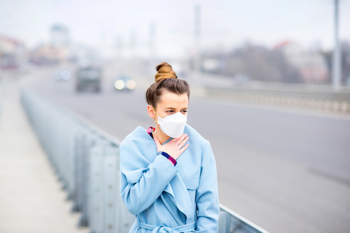 woman wearing dust mask in city