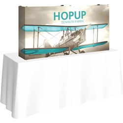 5ft Straight HopUp 2x1 Tabletop Fabric Trade Show Display with Full Fitted Graphic has a light weight, heavy duty frame that holds a fabric graphic mural. It sets up in seconds and can be packed away just as quickly after trade show or event