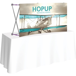 5ft Curved HopUp 2x1 Tabletop Fabric Trade Show Display with Front Graphic has a light weight, heavy duty frame that holds a fabric graphic mural. It sets up in seconds and can be packed away just as quickly after trade show or event
