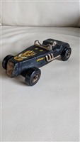 Handcrafted rough wooden HORNET car with a driver
