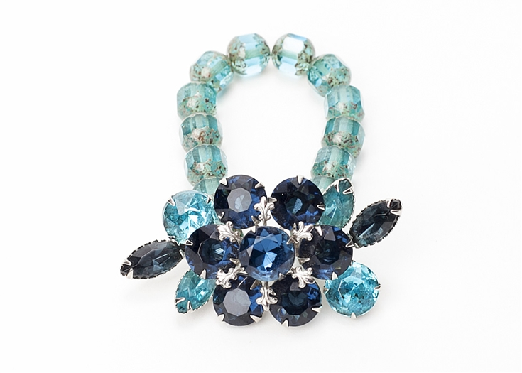Antique brooch in tones of blue, created into a one of a kind stretch bracelet using Aquamarine vintage beads. A truly stunning piece of arm candy from our Wear a Bracelet, Find a Cure Campaign.