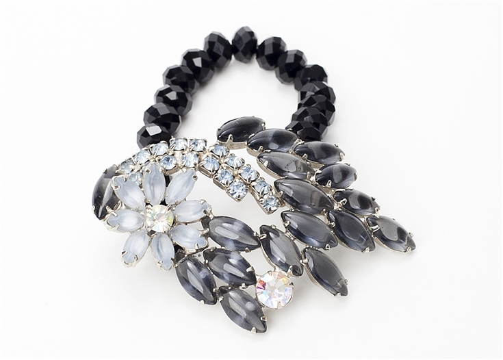 An antique brooch with crystals in tones of grey is created into a one of a kind stretch bracelet using black crystal beads. A truly stunning piece of arm candy from our Wear a Bracelet, Find a Cure Campaign.