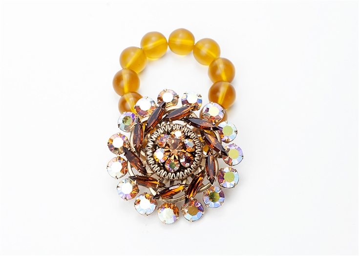 Antique marigold and amber crystal brooch created into a one of a kind stretch bracelet using golden beads. A truly stunning piece of arm candy from our Wear a Bracelet, Find a Cure Campaign.