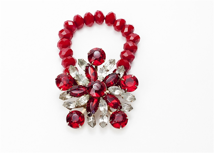 Antique ruby crystal brooch created into a one of a kind stretch bracelet using red vintage beads. A truly stunning piece of arm candy from our Wear a Bracelet, Find a Cure Campaign.