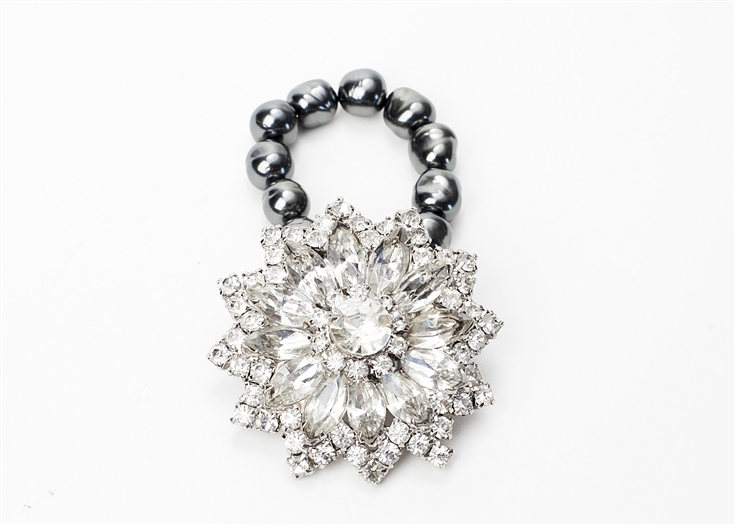 An antique brooch with clear crystal is created into a one of a kind stretch bracelet using dark grey pearls. A truly stunning piece of arm candy from our Wear a Bracelet, Find a Cure Campaign.