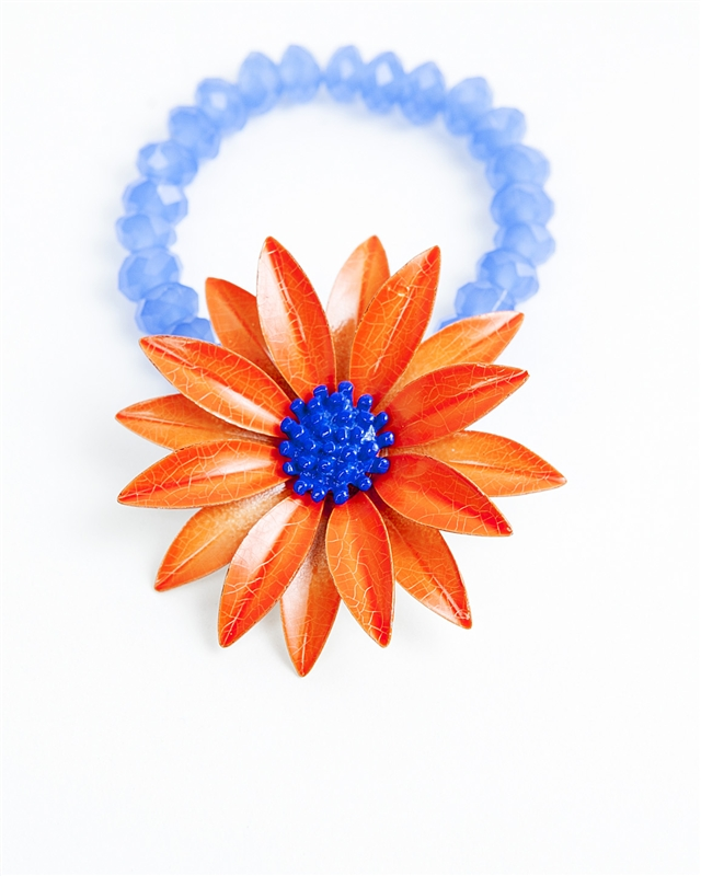 An one of a kind antique orange and blue floral brooch is paired with soft blue beads to create a truly stunning piece of jewelry from our Wear a Bracelet, Find a Cure Campaign.