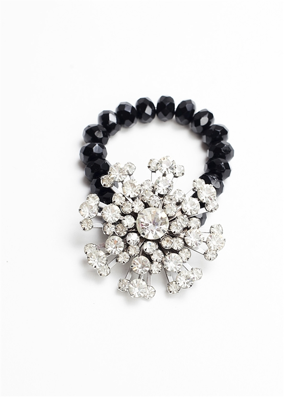 An antique crystal brooch is created into a one of a kind stretch bracelet using jet beads. A truly stunning piece of arm candy from our Wear a Bracelet, Find a Cure Campaign.