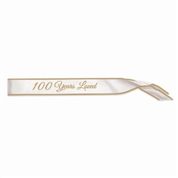The 100 Years Loved Satin Sash is white with 100 Years Loved displayed in gold lettering. Measures 33 inches long and 4 inches wide. Contains one per package. No returns.
