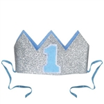 "The Glittered Baby's 1st Birthday Crown is a silver glittered crown with light blue lining and a blue ""1"" on the front. It has two detachable ribbon ties and measures 4 1/2 inches wide and 2 1/2 inches tall. Contains one (1) per pack. No returns."