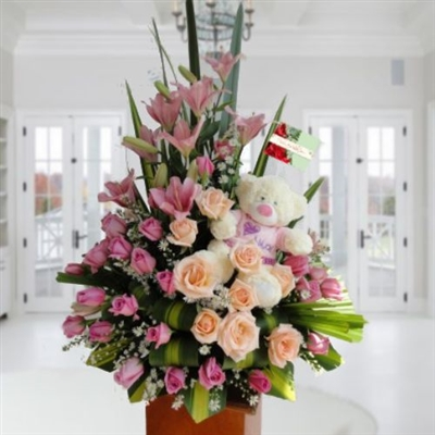 Pink and peach roses, lilies and teddy bear arrangement